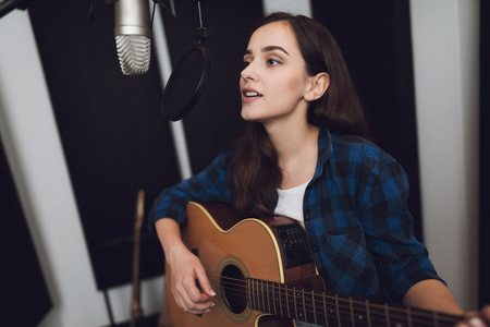 The girl is recording a song at a modern recording studio. She sings to the guitar. There is a microphone in front of her, she has an electric guitar in her hands. Stock Photo