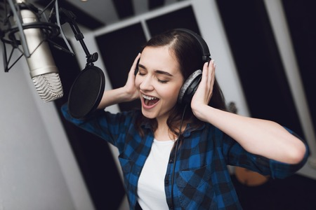 The girl sings her song in a modern recording studio. She sings the song very emotionally. In front of her is a studio microphone. Stock Photo