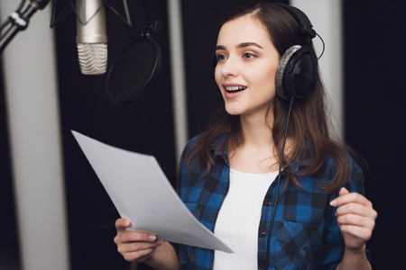 The girl in the recording studio sings a song. Her headphones are on her head. Next to her is a microphone. She emotionally sings the song.