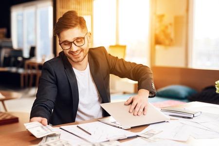 Freelancer man in black jacket counting money closing laptop sitting at desk.