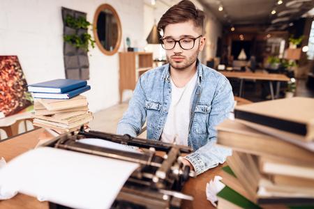 Freelancer man in jeans shirt typing at old typewritter sitting at desk.