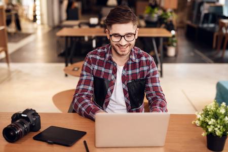Freelancer man wearing shirt and glasses typing at laptop sitting at desk.
