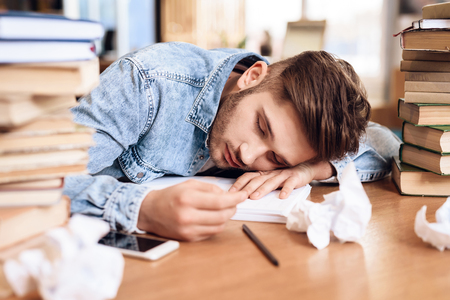 Freelancer man in jeans shirt sleeping at desk surrounded by books.