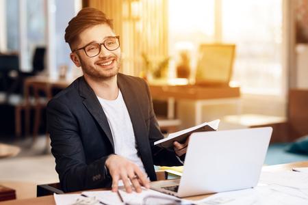 Freelancer bearded man in black jacket taking notes in notebook at laptop sitting at desk.