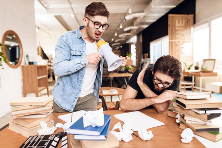 Two freelancer men in jeans shirt and t-shirt working at desk surrounded by books with one man screaming in megaphone. 版權商用圖片 - 96904168