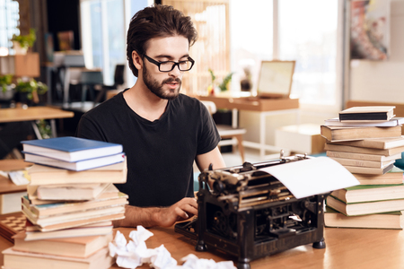 Freelancer bearded man in t-shirt typing at old typewritter sitting at desk. Stock Photo