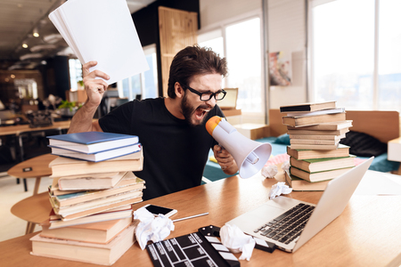 Freelancer man in t-shirt frustrated with notes at laptop sitting at desk surrounded by books.