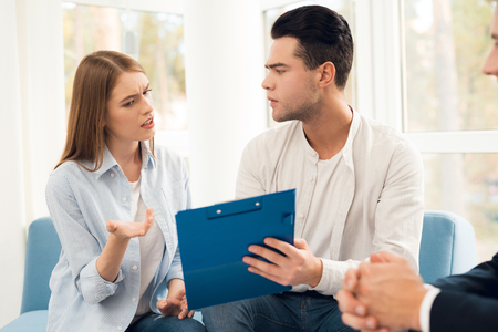 Young couple in a meeting with a realtor. A guy and a girl are discussing an agreement on the purchase of real estate.