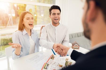 Jeune couple lors d'une réunion avec un agent immobilier. Un gars et une fille concluent un contrat avec un agent immobilier pour acheter une propriété. Une transaction réussie avec un agent immobilier. Le client serre la main de l'agent immobilier. Banque d'images - 96902369