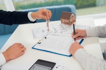 Stipula di un contratto per l'acquisto di beni immobili con un agente immobiliare. Foto ravvicinata del contratto e del progetto immobiliare. L'agente immobiliare fornisce all'uomo una chiave per il nuovo alloggio.
