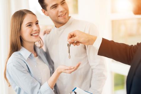 Junges Paar in einer Besprechung mit einem Makler. Ein Mann und ein Mädchen schließen mit einem Makler einen Vertrag über den Kauf einer Immobilie. Der Makler gibt dem Paar einen Schlüssel für das neue Gehäuse. Standard-Bild