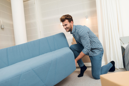 The guy moves the sofa while moving to a new home. The guy does a reshuffle in the room Stock Photo