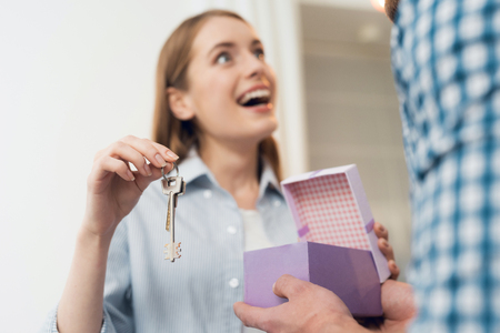 The guy gives his girl a box with a gift. The girl received a gift the key to new housing