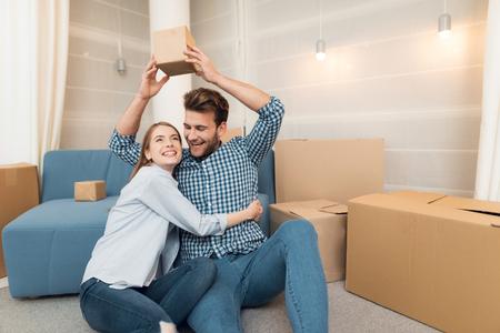 新しいアパートへの引っ越し中の若いカップル。新婚夫婦を新しい住宅に移す。彼らは箱の山の中に座っている。