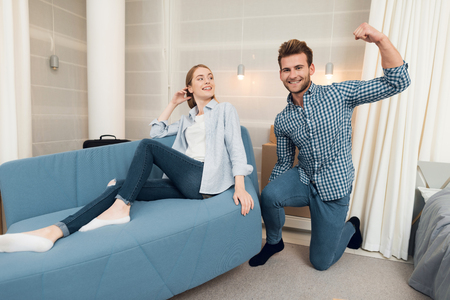 Young couple having fun while moving to new apartment. Moving newlyweds. Girl is sitting on a couch Stock Photo