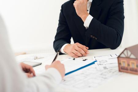 Abschluss eines Vertrages über den Kauf von Immobilien mit einem Makler. Nahaufnahmefoto des Vertrags- und Immobilienentwurfs.