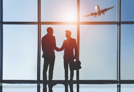 Silhouette view of two young businessmen are standing in modern office with panoramic windows. Standard-Bild