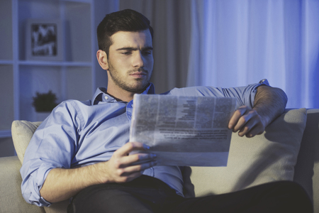 Young man is reading a newspaper at home.