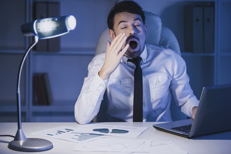 Exhausted young businessman is yawning at work in office. Standard-Bild
