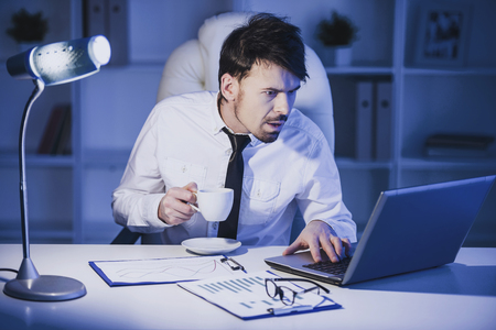 Surprised man is working on laptop in office and drinking a coffee