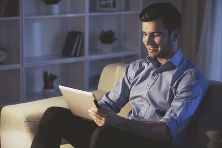 Smiling handsome man is using digital tablet at home. Side view. Standard-Bild