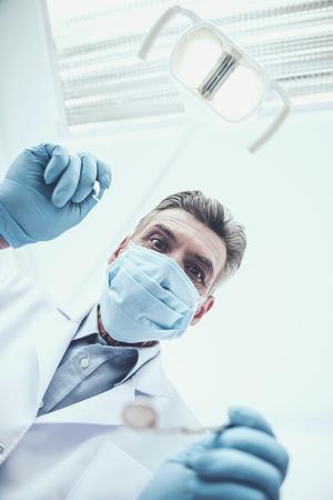 Portrait of a senior dentistin in mask in dental clinic.
