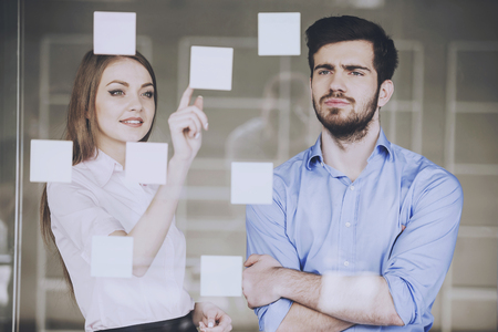 Young businessman and businesswoman working on new project with many sticky notes on glass screen in office.
