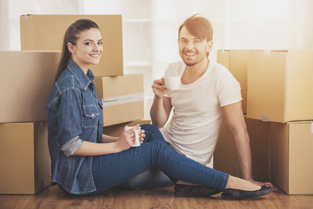 The young happy couple drinking tea and coffe. Moving, purchase of new habitation.
