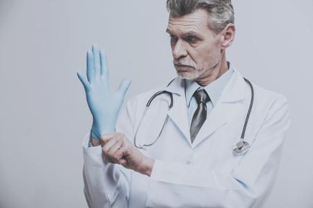 Senior male doctor wearing glove on grey background.