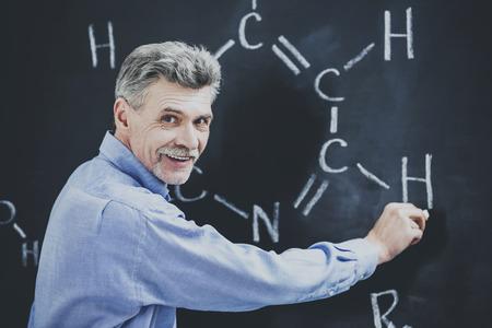 Professor of chemistry writes on the blackboard formula in University.