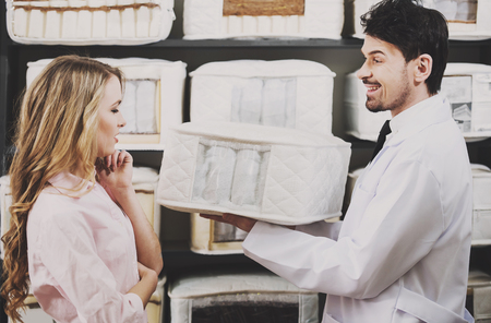 The young salesman tells the customer about quality mattresses in the store. Standard-Bild