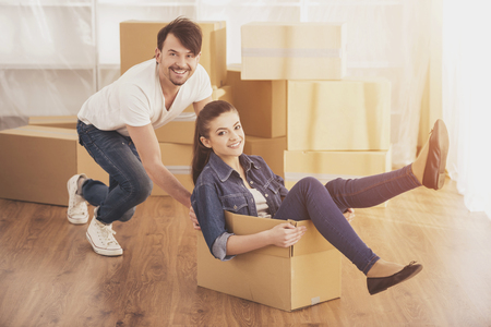 The young happy woman sitting in a cardboard box. Moving, purchase of new habitation.