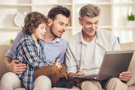 Generation portrait. Grandfather, father and son sitting and using laptop on sofa.