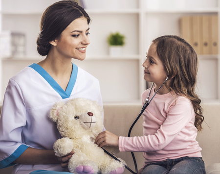 Young smiling female doctor and her little patient with teddy bear. Foto de archivo