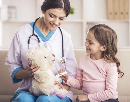 Young smiling female doctor and her little patient  with teddy bear.
