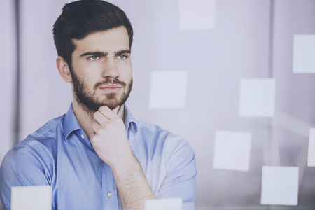 Young businessman working on new project with many sticky notes on glass screen in office.