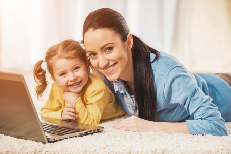 Young mother and her adorable daughter are using laptop while lying on the floor.