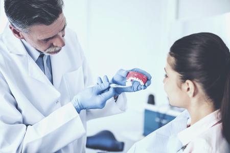 Cheerful dentist teaching on model of human teeth how right to brush teeth his female patient. Standard-Bild