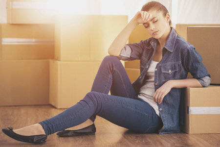 The young happy woman sits in a room near boxes. Moving, purchase of new habitation. Standard-Bild