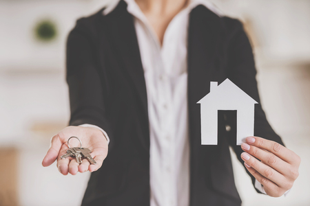 Close-up of hands of realtor woman is holding keys and model of home. Stock fotó