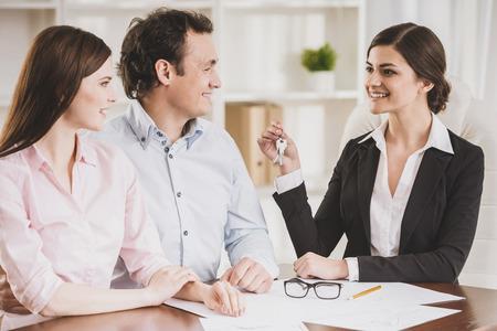 Jeune couple a signé un contrat financier avec une femme agent immobilier. Banque d'images