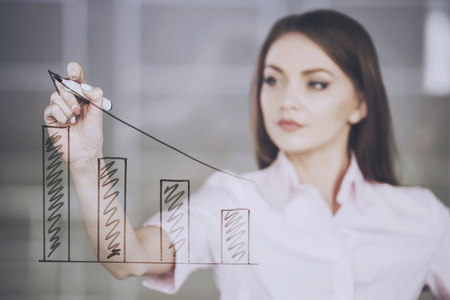 Young beauty businesswoman drawing a graph on glass screen in office.