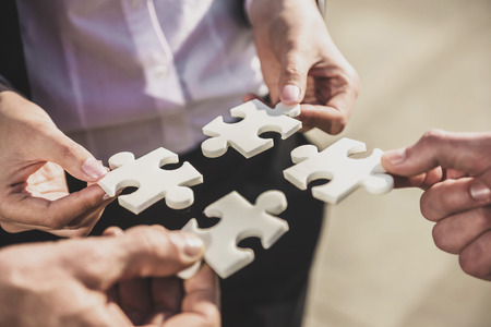 Closeup of business people wanting to put four pieces of puzzle together. Standard-Bild