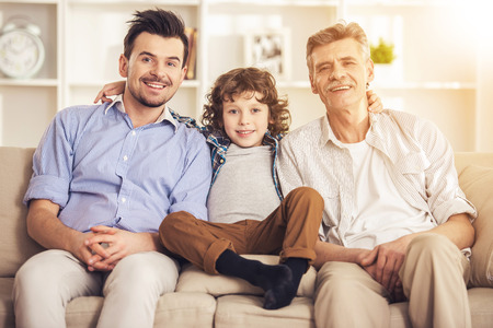 Generation portrait. Grandfather, father and son sitting on sofa.