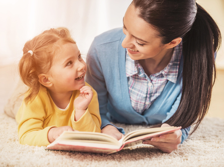 Young mother is reading a book to her cute daughter. Standard-Bild