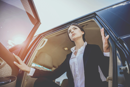 Young beautiful confident businesswoman in suit coming out of her luxurious car.
