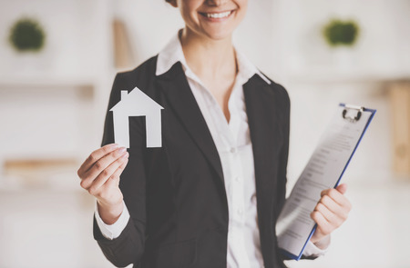 Happy realtor woman is holding model of home and smiling. Standard-Bild