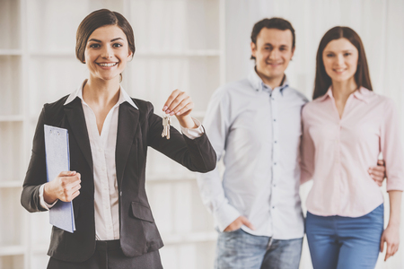 Realtor woman is holding keys and young couple on background.
