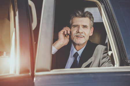 Mature handsome businessman coming out of his luxurious car and talking on the phone.