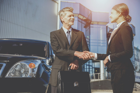 Two  successful confident businesspeople in suits   shaking hands standing near car. Standard-Bild